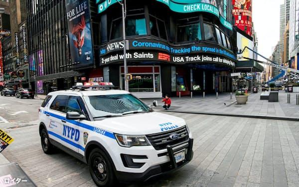 人通りが途絶えたタイムズクエアを警備するNY市警の車両=ロイター