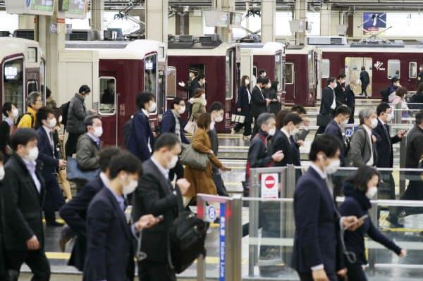 緊急事態宣言から一夜明け、電車で通勤する人たち。通勤客の人数に大きな変化はなかった(8日午前、阪急電鉄の大阪梅田駅)=玉井良幸撮影