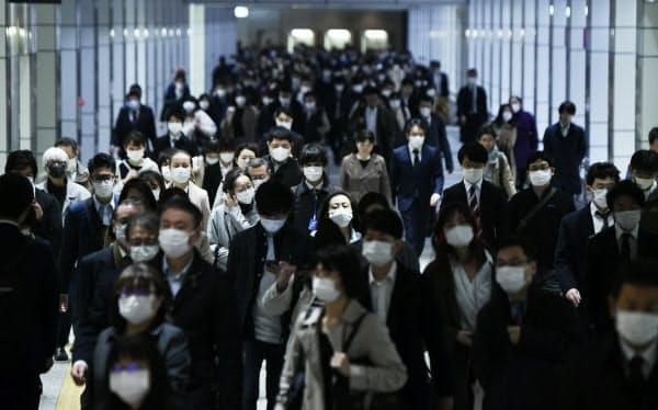 緊急事態宣言から一夜明け、マスク姿で通勤する人たち(8日午前)=中岡詩保子撮影