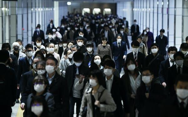 緊急事態宣言から一夜明け、マスク姿で通勤する人たち(8日午前、東京・新宿)=中岡詩保子撮影