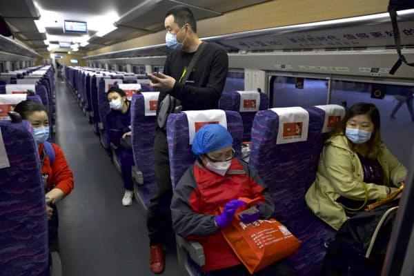 湖北省武漢市を出発する高速鉄道に乗車した人たち(8日)=AP