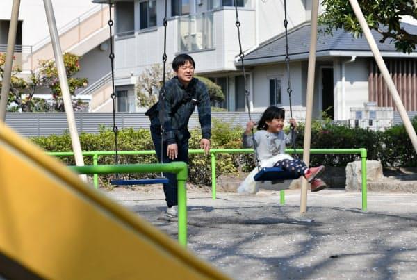 子どものブランコを押す練馬区に住む会社員の男性(40)。新型コロナウイルスの影響で保育園が休みになり、子どもたちの体調管理のためにも1日1回は外に出るというが、なるべく人と接触しないよう心掛けているという(8日午前、東京都練馬区)=藤井凱撮影