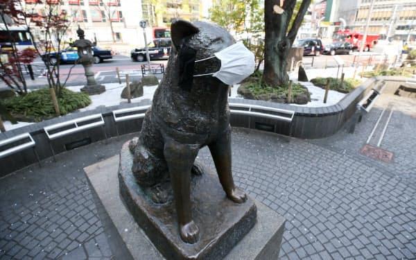 東京・渋谷の忠犬ハチ公像の口にはマスクが着けられています。スマホで像の写真を撮影した男性は、「買い置きしたマスクが足りなくなっているので、自分にも分けて欲しいくらいだ」と話した(8日午前)=樋口慧撮影