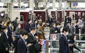 緊急事態宣言から一夜明け、電車で通勤する人たち(8日午前、阪急電鉄の大阪梅田駅)