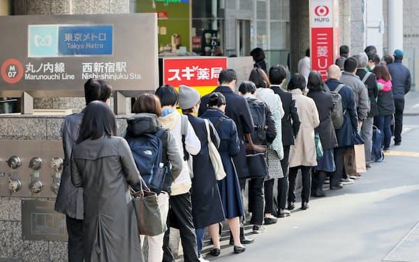 マスクを買い求めるため、開店前のドラッグストアに並ぶ人たち。開店30分前になると店員が購入希望人数を確認。店員が約40人の列後方に並んでいた人たちに「在庫切れです」と伝えると、がっかりした表情で列を後にする姿が見られた(東京都新宿区)=樋口慧撮影