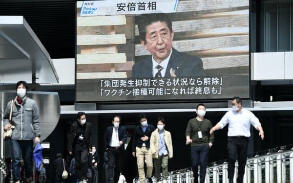 緊急事態宣言の発令についてのニュースが流れる街頭モニター(8日午前、東京都千代田区)=中岡詩保子撮影