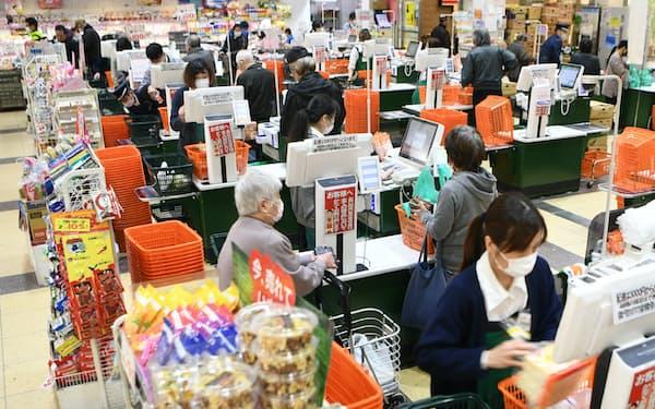 スーパーの越前屋は客の密集を避けるため、3月下旬からレジの数を6台から12台に増やした。店員はマスクを着用して接客する(8日午前、大阪市西成区)=目良友樹撮影