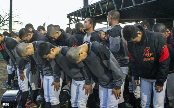 選抜高校野球大会の中止決定後、練習を終えてグラウンドへ一礼する長崎・創成館高ナイン(3月11日)=共同