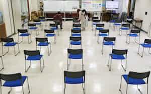 博多区役所で間隔を空けて座り、手続きの順番を待つ家族連れ(8日、福岡市)