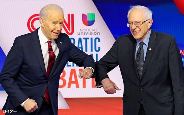 3月15日、米民主候補のテレビ討論会で握手代わりに肘をぶつけるバイデン前副大統領(左)とサンダース上院議員=ロイター