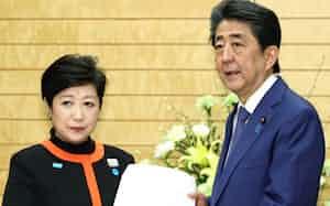 新型コロナウイルスへの対応を巡り、小池東京都知事(左)から緊急提言を受け取る安倍首相(26日、首相官邸)