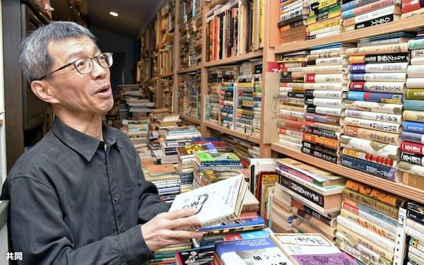 1人で本の編集や販売を続ける「亀鳴屋」の勝井隆則さん。書棚にはこれまでに読んだ多数の本が並ぶ(金沢市)=共同