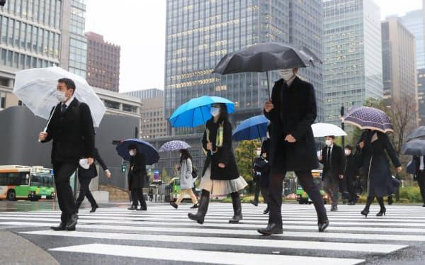 雨の中、通勤する人たち(13日午前、東京・丸の内)