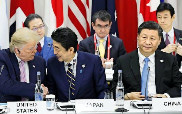 G20大阪サミットで握手するトランプ米大統領(左)と安倍首相。右は中国の習近平国家主席(2019年6月、大阪市)=共同