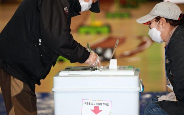 マスクとビニール手袋を着用して投票する有権者(15日、ソウル)