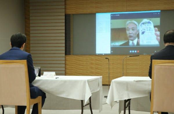 マスクや消毒液、防護服などのメーカートップらとテレビ会議で話す安倍首相(手前左)=15日、首相官邸