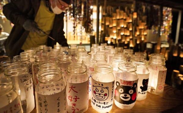 熊本県益城町の木山仮設団地で、犠牲者を悼みともされたキャンドル(16日未明)=共同