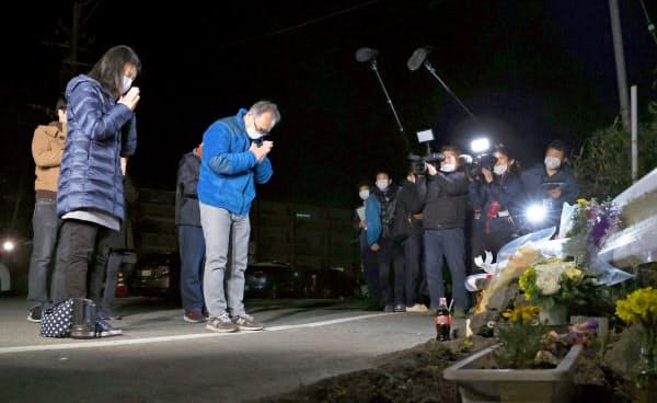 大和晃さんが犠牲になった阿蘇大橋の崩落現場付近を訪れ、手を合わせる母忍さん(左)と父卓也さん(16日未明、熊本県南阿蘇村)=共同