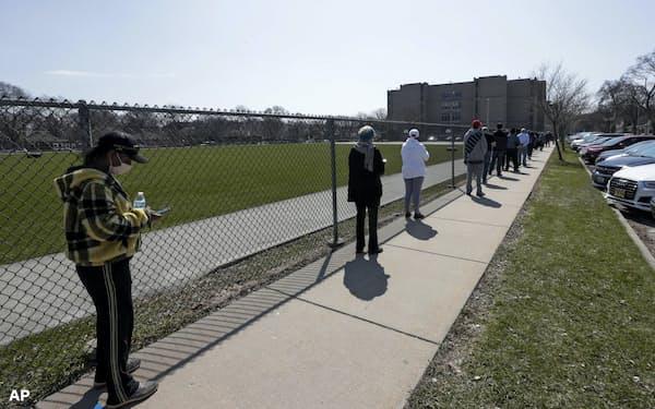 新型コロナの感染を防ぐため、距離を開けて投票の列に並ぶ有権者(7日、ウィスコンシン州ミルウォーキー)=AP