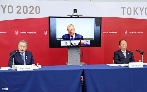 テレビ電話方式の合同会議を終え、記者会見するIOCのコーツ調整委員長(中央の画面)、組織委の森喜朗会長(左)ら(16日午後、東京都中央区)=代表撮影、共同