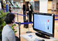 羽田空港で行われたサーモグラフィーを使った搭乗客の検温(17日午後)=共同