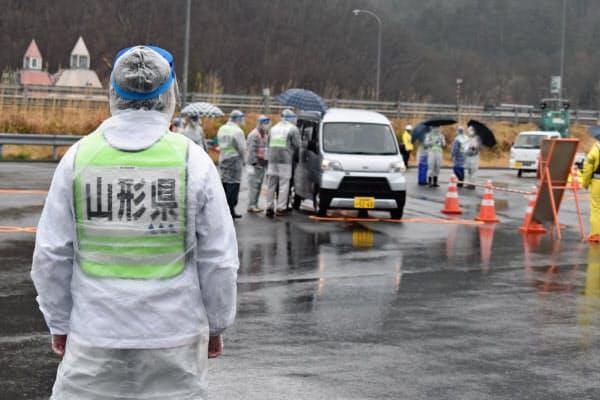 フェースシールドなどをつけた県職員がドライバーに検温に協力を呼びかける(18日、山形市の山形蔵王パーキングエリア)