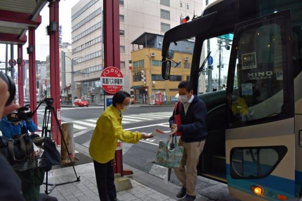仙台~山形間の高速バスを降りる乗客にチラシを配る県職員(18日、山形市)