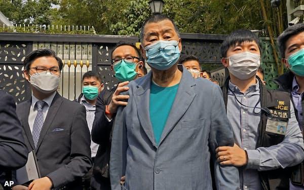 18日、自宅前で警察に連行される香港紙創業者の黎智英氏(中)=AP