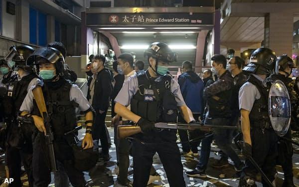 新型コロナで大人数の抗議活動は難しくなっている(2月、マスク姿で警戒する警察官)=AP