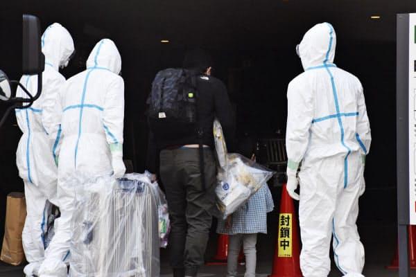 入院中の医療機関から療養先となるホテルに到着した人たち(中央)(15日午後、さいたま市)=共同