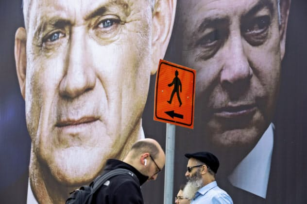 リクードのネタニヤフ首相(右)と「青と白」トップのガンツ氏は連立政権の樹立で合意した(テルアビブ郊外に張られた選挙ポスター)=AP