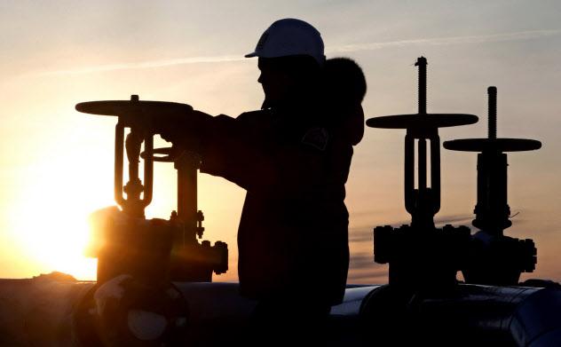 ロシアの西シベリアの油田地帯でバルブを点検する作業員=ロイター