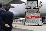 貨物機から降ろされる、台湾当局から寄贈されたマスク(21日午前、成田空港)=共同