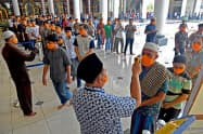 イスラム教の金曜礼拝で検温を受ける信徒(3月、東ジャワ州スラバヤ)=ロイター