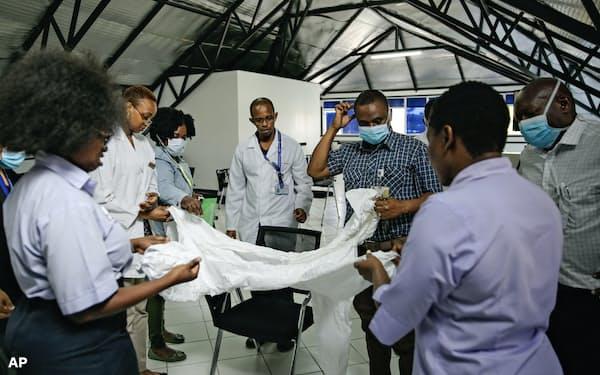 途上国では感染症対策のための資金が慢性的に不足している(ケニアの首都ナイロビで防護服の説明を受ける医療関係者)=AP