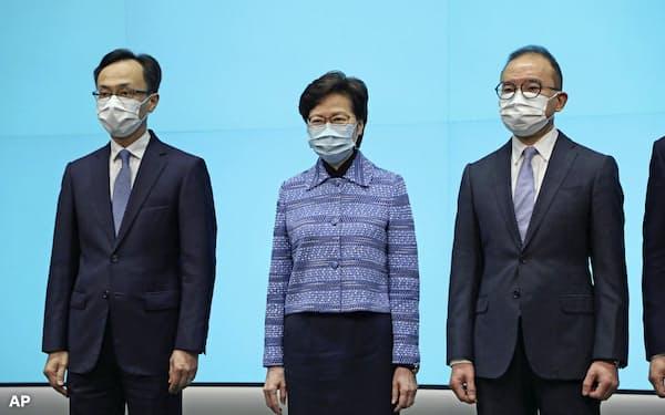 閣僚の交代を発表する林鄭長官(中)(22日、香港)=AP