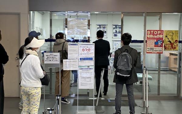 混雑する銀行では「60分待ち」の案内も(22日午前、千葉県内)