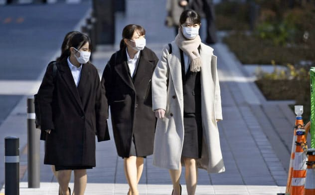 マスク姿で合同会社説明会の会場に向かう就職活動の学生ら(3月、東京都港区)=共同