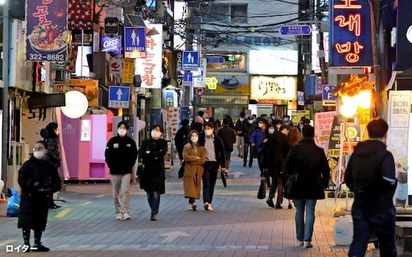 ソウル中心部をマスク姿で歩く人たち(22日)=ロイター