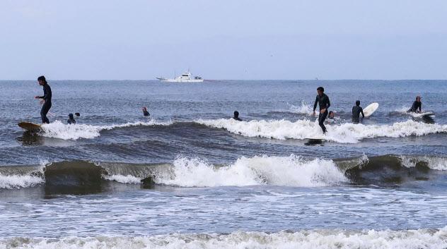 江の島近くの海岸で、波乗りを楽しむサーファーたち(22日、神奈川県藤沢市)=共同