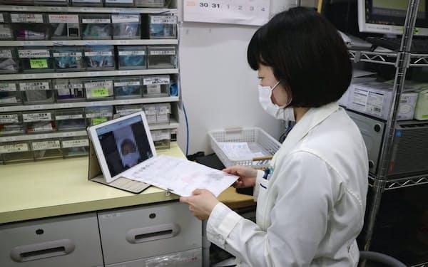 薬剤師がテレビ電話で患者とやりとりする(東京都港区の「ナチュラルローソンクオール薬局城山トラストタワー店」)=一部画像処理しています