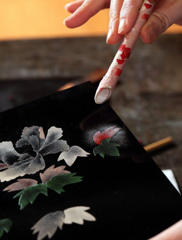 漆で描いた模様に金銀粉を振りかけ、漆器を装飾する「蒔絵」=玉井良幸撮影
