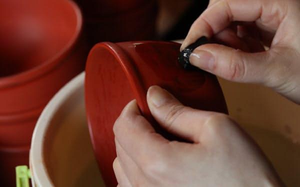 朱塗りの表面を炭で削り、下塗りの黒漆を模様として浮かび上がらせる「研ぎ出し」