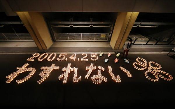 ろうそくの明かりで浮かび上がった「2005・4・25 わすれない」の文字(24日、兵庫県尼崎市)