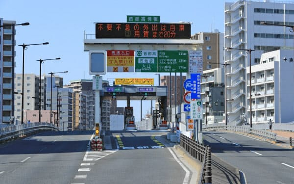 「不要不急の外出は自粛」と表示された首都高速道路の西池袋入り口(25日午前、東京都豊島区)