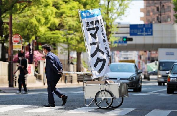 リヤカーを引いてマスクを販売する男性(25日午前、福岡市)