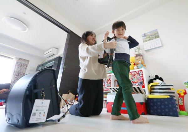 自宅でランドセルを試着する砂田孝太郎くん(右)と母親の沙矢香さん(25日午前、千葉市美浜区)
