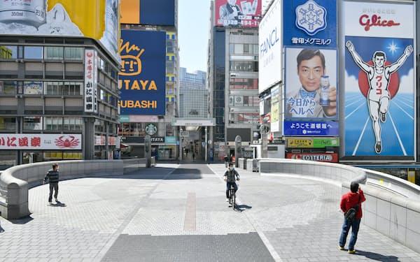 つい数カ月前までは世界各地から観光客が訪れていた大阪・ミナミ。「グリコサイン」がシンボルの道頓堀の戎橋は、連休初日にも関わらず人通りはまばら。飲食店の多くが臨時休業となった商店街には「がんばれミナミ がんばれ大阪!!」のメッセージが連なる。「なにわの台所」として親しまれる「黒門市場」では、食べ歩きを楽しみに詰めかけていたインバウンドが途絶えた。青果店を営む安井道代さん(73)は「少しずつ休業する店が出てきた。いつまでこの状況が続くのか」と不安げに話す。                                                   人通りが少ない道頓堀の戎橋(25日午前、大阪市中央区)