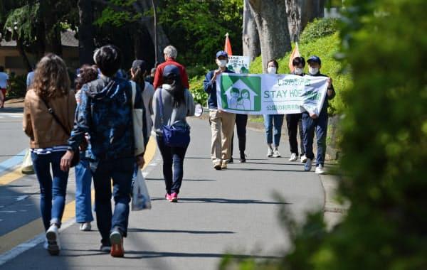 横断幕を掲げて公園の利用自粛を呼びかける東京都公園協会の職員(25日午後、東京都世田谷区の駒沢オリンピック公園)