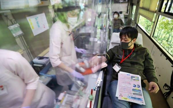 イオンモール香椎浜の駐車場に設けられた献血会場で献血する人たち(25日午後、福岡市)